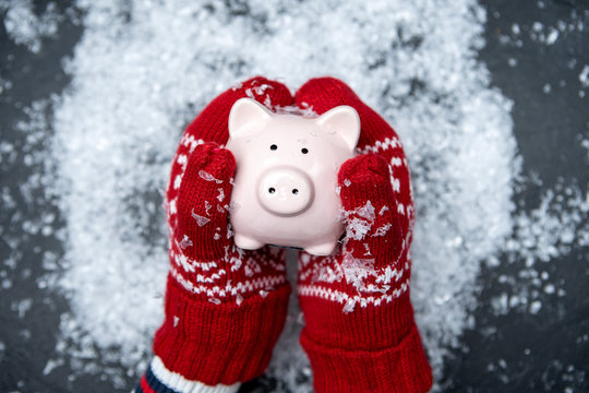 Image of man's hands in red mittens holding piggy bank