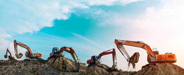 Many excavators work on construction site at sunset,panoramic view Fotomurales