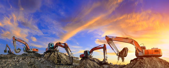 Many excavators work on construction site at sunset,panoramic view Wall mural