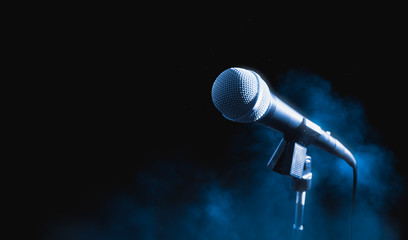 microphone on a stand on a dark background with smoke
