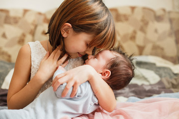 Little sister hugging her newborn brother. Toddler kid meeting new sibling. Cute girl and new born baby boy relax in a home bedroom. Family with children at home. Love, trust and tenderness