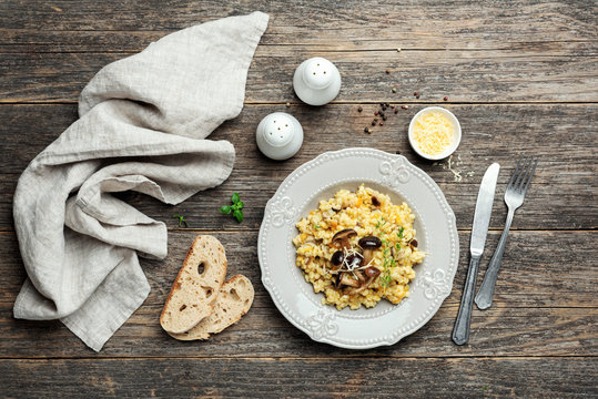 Pearl barley mushroom risotto on wooden background. Top view
