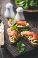 Salmon and avocado toast, healthy appetizer or snack on wooden serving boarc. Closeup view
