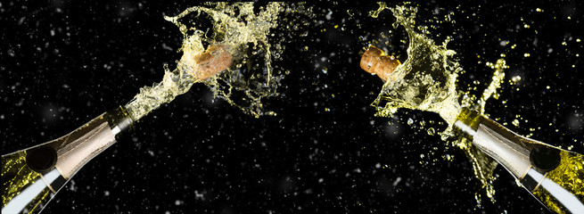 Celebration theme with splashing champagne bottles on black background with snow. Christmas or New Year, Valentines day background.