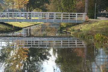 wooden white bridge over ditch in the autumn season in public park Schakenbosch in Leidschendam