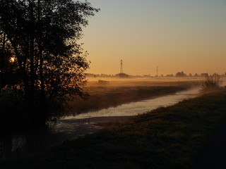Sunrise with morning fog over the meadows of the polder at Goudarak close to Gouda in the Netherlands