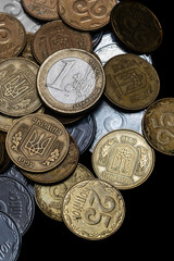 Ukrainian coins with one euro coin isolated on black background. Close-up view. Coins are located at center of frame. A conceptual image.
