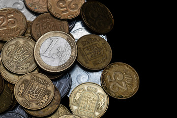 Ukrainian coins with one euro coin isolated on black background. Close-up view. Coins are located at the left side of frame. A conceptual image.