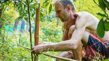 A caucasian man using bamboo wood for building natural fence in the garden