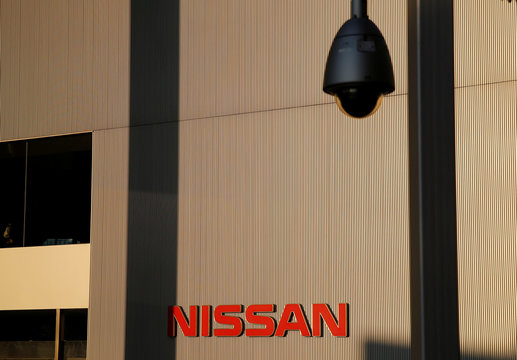 The Nissan logo is seen behind a surveillance camera at Nissan Motor Co.'s global headquarters building in Yokohama