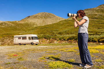 Camper car and tourist with camera in mountains