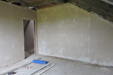 Walls of an empty room under construction covered with hard plaster and some mess