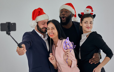 The four happy business people taking christmas selfie