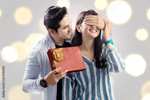 Happy asian man covering his girlfriend eyes while giving