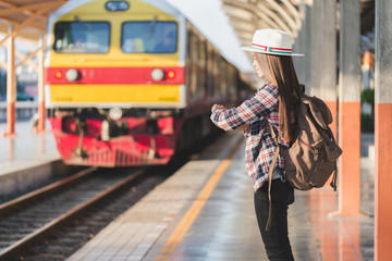 Beautiful young asian woman traveler looking clock  with brown bag ,Waiting for train at train station, Chinese tourists, Travel and vacation concept.