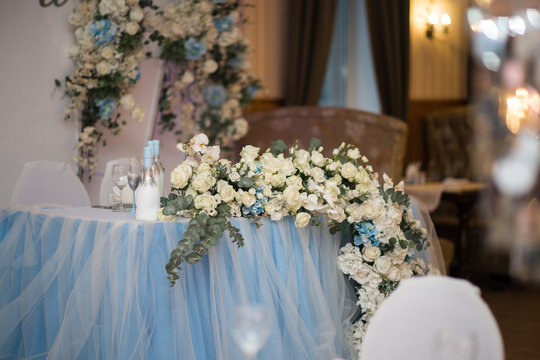 Wedding presidium in restaurant, free space. Wedding banquet table for newlyweds with flowers, greenery, pink cloth and bulbs. Lush floral arrangement on wedding table. Luxury wedding decorations
