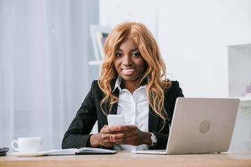 african american businesswoman holding smartphone near laptop in office