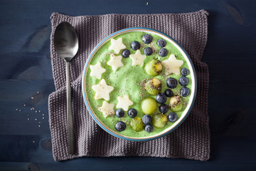 healthy green spinach smoothie bowl with blueberry, apple stars, kiwi, chia seed
