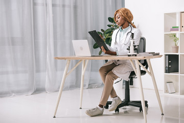 confident african american scientist sitting with stethoscope and holding clipboard