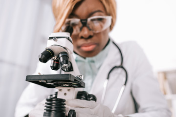 selective focus of microscope with female african american scientist on background
