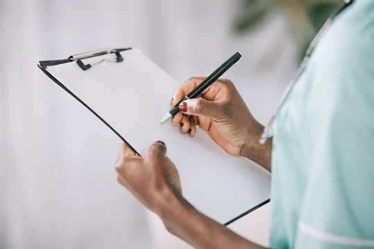 cropped view of african american nurse writing in clipboard with paper