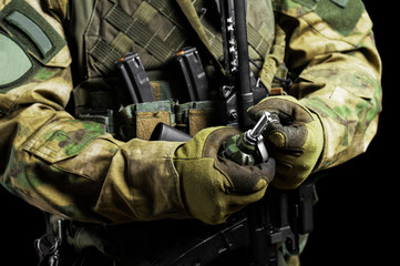 Soldier in full combat ammunition pulls a check from a grenade.