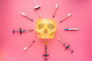 Flat lay of medical instruments with human skull on rose background. Mock up health care medical background.