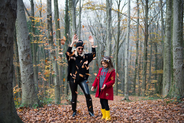 Cute girl and mom playing with leaves in the forest at autumn
