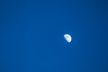A half of white bright moon on a clear blue sky, calm beautiful view.