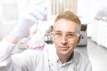 Badanie laboratoryjne. Naukowiec trzyma próbówkę z roztworem.