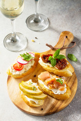 Italian Antipasti snacks set for Wine. Brushetta with Soft Cheese, Pear, Radish, Salmon and Dried Tomatoes on a light stone background.