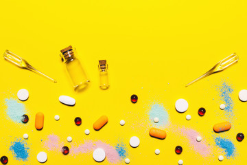 Yellow medical pharmaceutical background. Multicolored pills top view. childhood diseases. place for text. Copy space