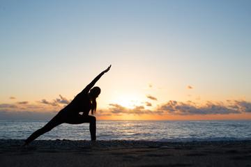 Human silhouette doing yoga on the beach at dusk