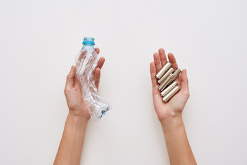 Sparate your trash. Two human hands are holding plastic and batteries isolated