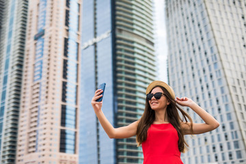 Portrait of young smile woman in red dress, sunglasses and summer hat take selfie on the phone on downtown skycrapers background