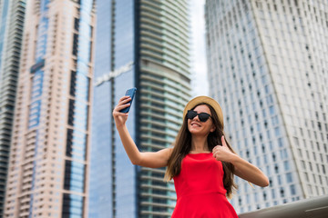 Portrait of young smile woman in red dress, sunglasses and summer hat make video call with thumbs up on the phone on downtown skycrapers background