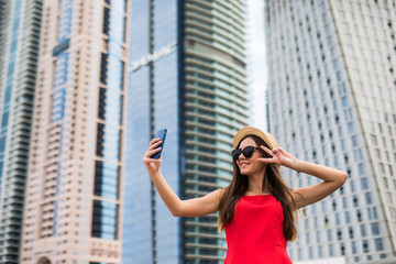 Portrait of young smile woman in red dress, sunglasses and summer hat make video call with victory sign on the phone on downtown skycrapers background