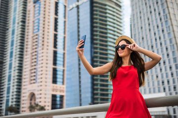 Portrait of young smile woman in red dress, sunglasses and summer hat make selfie or video call on the phone on downtown skycrapers background
