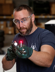 Rodger Brown checks the alignment of a front sight post assembly with a laser sight, at Spike's Tactical LLC, a gunmaker in Apopka