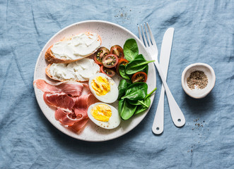 Cream cheese toast, boiled egg, prosciutto, spinach, tomatoes - delicious healthy breakfast or snack on blue background, top view