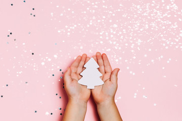 Child's hands holding big snowflakee in hands on sparkling pink background. Bright and festive Christmas and New Year picture. Top view, flat lay.