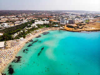 Cyprus beautiful coastline, Mediterranean sea of turquoise color. Houses on the Mediterranean coast. Tourist town with a Long beach. Summer vacation at sea. top view, aerial view. Cyprus, Ayia NAPA