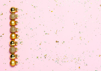 Christmas background with golden decorations put as frame on pink background. Bright and festive flat lay. Top view, Copyspace for text. Greetings for christmas or new year.