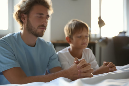 Father with son praying near bed at home