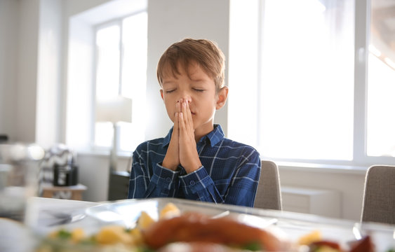 Little boy praying before meal at home