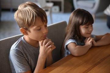 Cute children praying at home