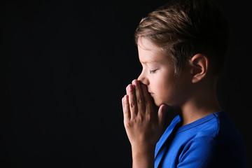 Portrait of praying boy on dark background Wall mural
