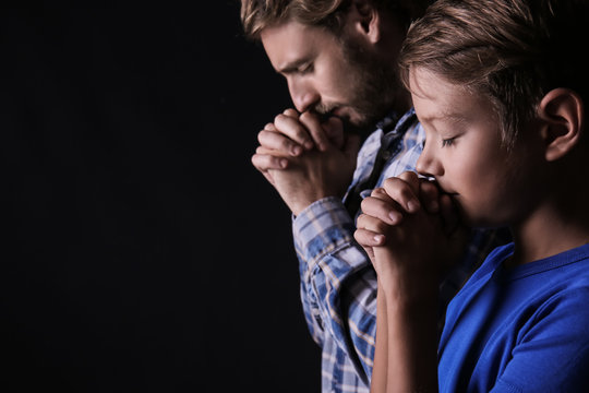 Praying father and son on dark background