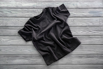 Blank black t-shirt on wooden background
