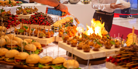 Cocktail Reception at the event, cook fry on fire, Shrimps, burgers, salads, seafood on wooden boards, with sprouted greens